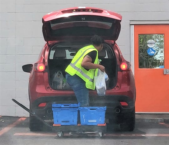 Touchless grocery shopping: a Walmart employee does the shopping and delivers groceries right to a customer's vehicle. Please return those plastic bags to Walmart – not your blue recycling bin.