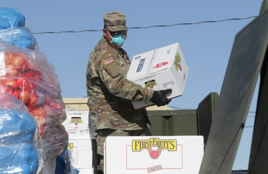 New Mexico Army National Guard member Pfc. Edwin Rodriguez carries a box of apples as part of a donation by the State of New Mexico to the Navajo Nation on April 15, 2020 in Sheep Springs.