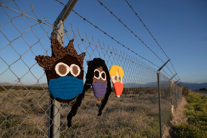"""Knitted faces with masks are displayed on a fence along Palm Drive in Desert Hot Springs, Calif., on April 17, 2020. A Facebook post from the previous day had a photo of the yarn art with a longer banner that read, """"WE'LL RISE ABOVE THIS."""""""