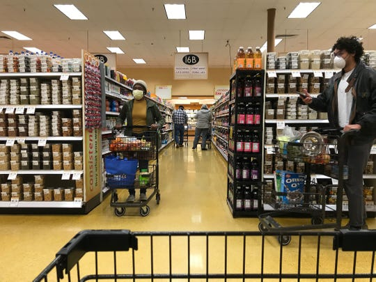 Staff and customers at Wegmans store on Hylan Drive in Henrietta wore masks Saturday, April 17, 2020.   Customers pause to let each other go past.