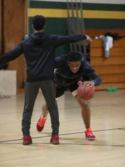 Christian Simmons former School of the Arts player works out with friend Simeon Heard who just finished up his last year playing basketball for D'Youville College.  The two, once competitors, have worked out together off season and helped each other grow as college basketball players. Heard, a former basketball player at The Charles Finney School in Penfield, works with Simmons at the school's gym Saturday, April 17, 2020.  Simmons practices a quick move around Heard before shooting.