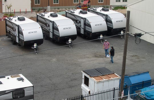 Joel Alvarez, points at one of the trailers as he talks to another person on Thursday, April 16, 2020. The trailers are parked next to the Chinatown Navigation Center.