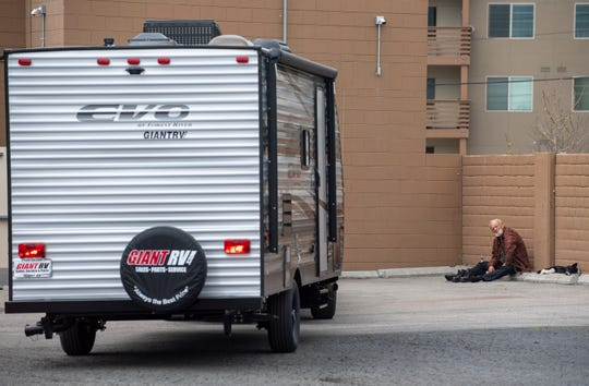 James Prola, 58, sits next to his dog Nalu as he watches the trailers be parked in Chinatown Navigation Center's parking space on Thursday, April 16, 2020.