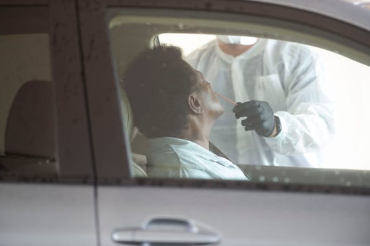 """Allied Health examiners test people for coronavirus during a drive-thru testing Saturday, April 18, 2020, at Dreamland Park in Fort Pierce. Fort Pierce Commissioner Reggie Sessions teamed up with Allied Health and M Care Medical Center to offer the free testing. """"When you look at the numbers... a lot of it is happening in African American communities,"""" Sessions said. """"I noticed there hasn't been a lot of testing sites in the center of those communities. This is making it convenient and free for them. This is a win-win to save a life."""" Testing continues April 20 and 21. To be prescreened for a test and to make an appointment, call 772-940-1020."""