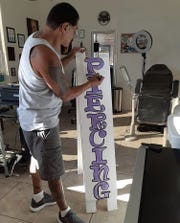 Robert Barrozo works on a sign inside Tattoo Dreams 4u, a tattoo and piercing shop he and his wife recently opened in Fillmore, before the coronavirus forced them to close.