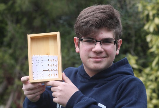 Paul Coschignano, a 13-year old developer from Eastchester, holds up a box of ear clips that he developed on a 3D  printer in his Eastchester home April 17, 2020. The ear guard keeps a surgical mask off the ears.