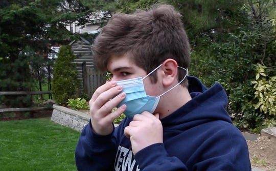 Paul Coschignano, a 13-year old developer from Eastchester, puts on a surgical mask as he demonstrates an ear clip that he developed on a 3D  printer in his Eastchester home April 17, 2020. The ear guard keeps a surgical mask off the ears.
