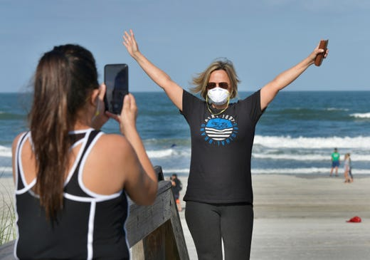 Delcia Dias (left) and Monica Dias celebrate the beaches opening on a limited basis during the coronavirus pandemic Friday, April 17, 2020 on Jacksonville Beach, Florida. The beaches are open from 6 a.m. to 11 a.m. and then 5 p.m. to 8 p.m. for activities such as walking, running, surfing, swimming, fishing and other activities. No sunbathing or sitting is allowed.
