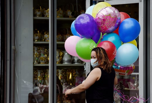 A woman wearing a face mask to protect herself from the coronavirus carries balloons for a birthday party  on April 18, 2020, in Arlington, Virginia.