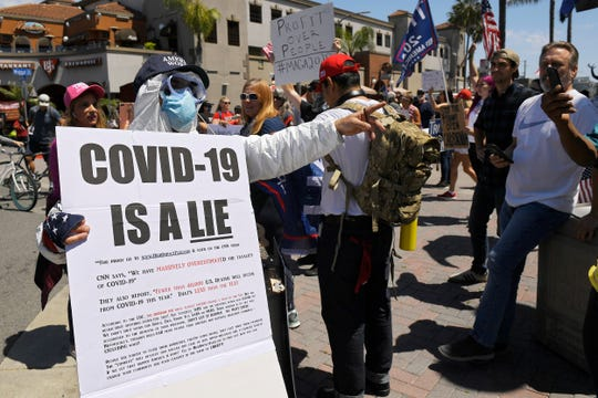 Protesters demonstrate against stay-at-home orders that were put in place due to the COVID-19 outbreak, Friday, April 17, 2020, in Huntington Beach, Calif. (AP Photo/Mark J. Terrill) ORG XMIT: CAMT117