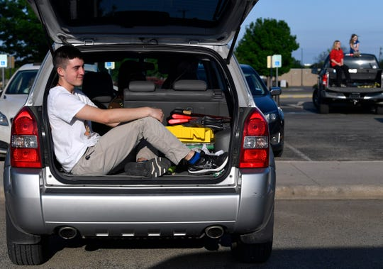 Will Hampton sits with the tail gate open, listening to the music performed by a praise band Saturday at Hendrick Medical Center.