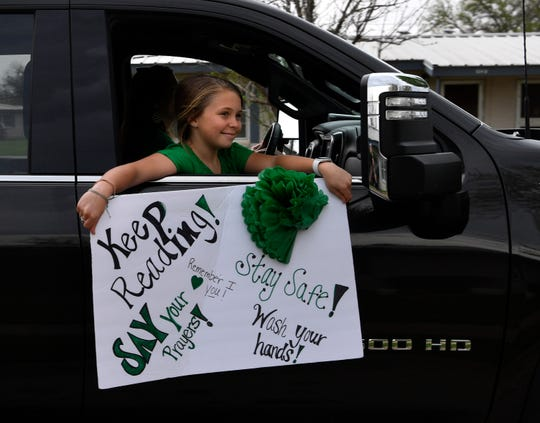Kadynce Kennedy, 11, waves a sign at residents in a Breckenridge neighborhood as she rides with her mother Shelby, a second-grade teacher, in a parade of educators through town March 27.