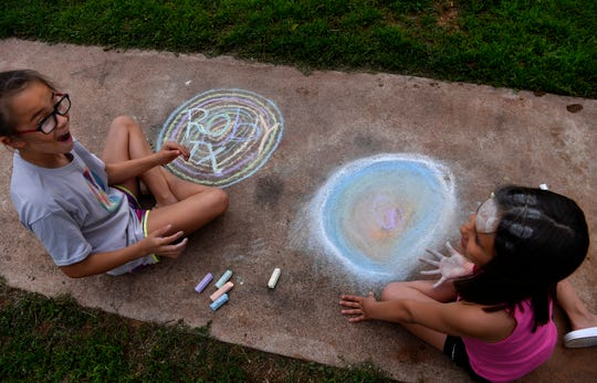 Mazer Hernandez, 10, (left) laughs as she reacts to her friend Kamryn Field, 7, after she planted her chalk-covered hand on her own forehead. The girls were sitting on a sidewalk in Roby March 27, passing the time before social distancing had become the norm.
