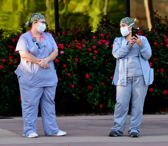 Personnel from Hendrick Medical Center watch the Drive-In Worship service from the hospital sidewalk Saturday.