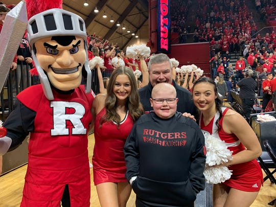 Joey Koslowski, center, stands in front of his father, Joe, during a Feb. 9 Rutgers University home basketball game