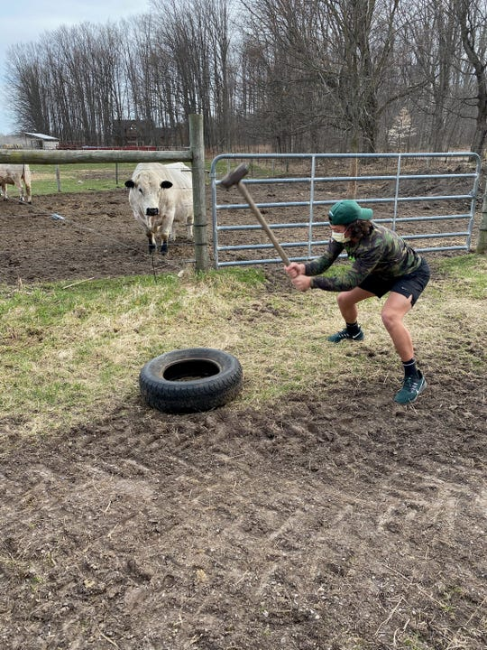 Michigan State walk-on wide receiver Nick Hunter hits a tractor tire with a sledgehammer at his former Grayling HIgh teammate Eli Jackson's family farm.