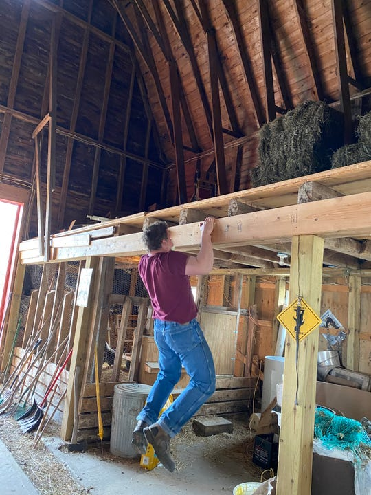 Eli Jackson, a senior at Grayling High who plans to play football at Alma College this fall, does pull-ups in his family's barn.