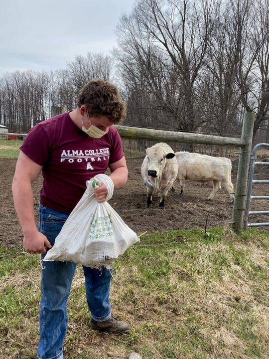 Eli Jackson curls bags of rocks during his weightlifting training at his family's farm near Grayling.