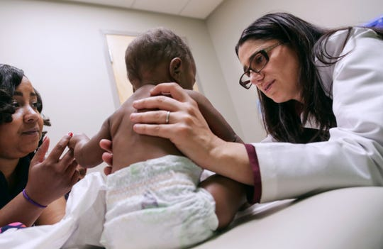 Dr. Mona Hanna-Attisha, pediatrician at Hurley Medical Center, talks with Flint resident Courtney Dudley while examining her daughter, Isabella Evans, during a wellness appointment at the Hurley Children's Center in downtown Flint in April 2016.