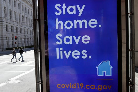 A sign advising people to stay home due to COVID-19 concerns is displayed April 2 at a MUNI bus stop in San Francisco.
