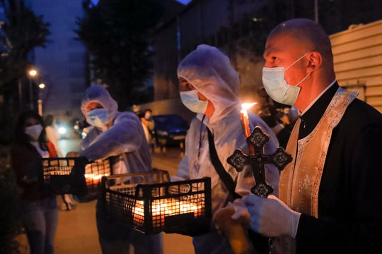 A priest distributes holy light to households Saturday during the coronavirus pandemic in Bucharest, Romania. Priests accompanied by volunteers distributed the holy light ahead of the usual time, at midnight, as people observed the interdiction to join religious celebrations in the week leading to the Orthodox Easter, imposed across Romania as authorities try to limit the spread of the COVID-19 infections.