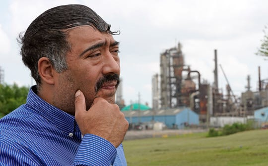 Juan Flores stands in a small park near a refinery along the Houston Ship Channel Monday, March 23, 2020, in Houston.