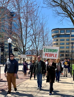 About 70 people walked around the Wisconsin State Capitol on Sunday, April 19, 2020, carrying signs that protested Gov. Tony Evers' order to stay home. Three groups plan rallies at the Capitol on Friday, April 24.