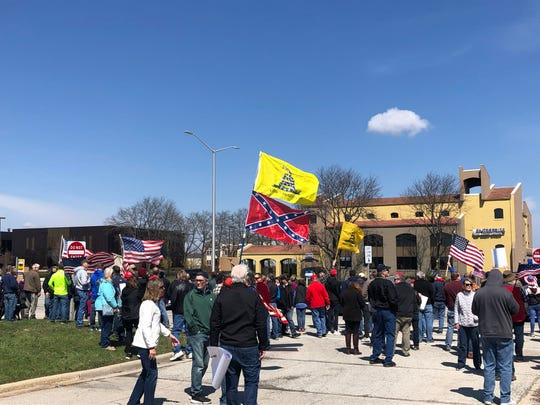A photo from a rally in Brookfield on Saturday, April 18, 2020, shows two men in plaid, both holding Don't Tread on Me flags.