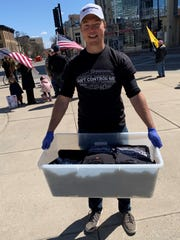 """Colin Guest, 22, distributed free T-shirts at a Sunday rally at the Wisconsin State Capitol. The shirts said """"can't control me."""""""