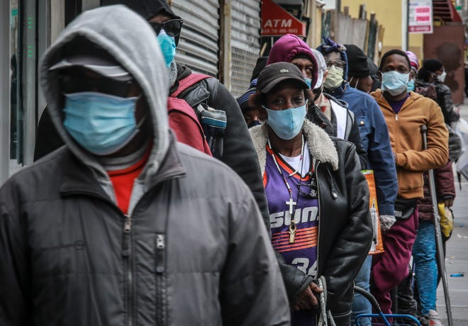 People wait for a distribution of masks and food from the Rev. Al Sharpton in the Harlem neighborhood of New York, after a new state mandate was issued requiring residents to wear face coverings in public due to COVID-19 on Saturday. The latest Associated Press analysis of available data shows that nearly one-third of those who have died from the coronavirus are African American, even though blacks are only about 14% of the population.