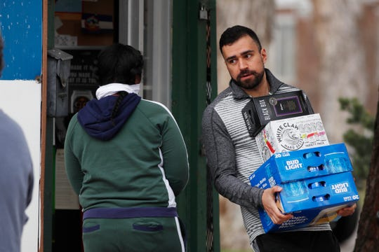 """As one shopper enters, another shopper carries his goods out of a liquor store minutes after Denver Mayor Michael Hancock issued a """"stay at home"""" order to reduce the spread of the new coronavirus Monday, March 23 in Denver."""