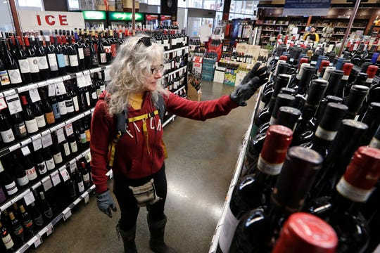 """Lisa MacDonald shops for wine in a liquor store in Seattle on March 25. In many states, liquor stores are cl""""essential businesses"""" and have remained open during the COVID-19 pandemic."""