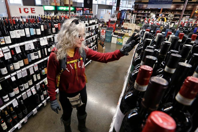 "Lisa MacDonald shops for wine in a liquor store in Seattle on March 25. In many states, liquor stores are cl""essential businesses"" and have remained open during the COVID-19 pandemic."