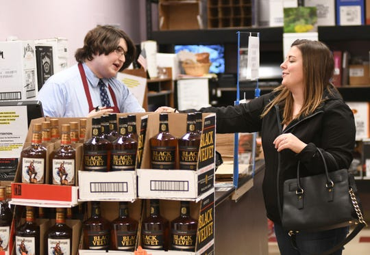 Jacob Lockwood, left, a manager in training for Sparkle Market in Andover, Ohio, checks the driver's license of Lauren Seman on April 14. Alcohol sales have enjoyed a large jump since the beginning of the COVID-19 pandemic.