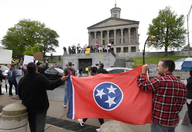 Protesters hold a Tennessee state flag during the rally against the stay-at-home orders at the State Capitol Sunday, April 19, 2020 in Nashville, Tenn.