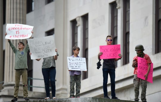 Protesters hold signs during the rally against the stay-at-home orders at the State Capitol Sunday, April 19, 2020 in Nashville, Tenn.