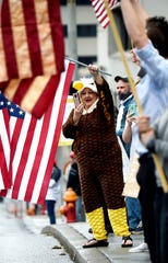 Tammy Sharp in an eagle costume waves a flag during the rally against stay-at-home orders at the State Capitol Sunday, April 19, 2020 in Nashville, Tenn.