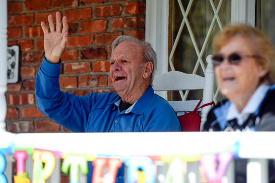 Len Zwerver waves from his front porch with his wife Doris as the Woodland Park fire department, along with family and friends, drive by to surprise Len for his 92nd birthday on Sunday, April 19, 2020.