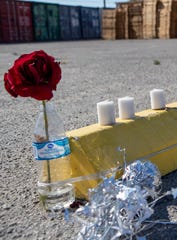 A flower and candles rest at the parking spot of an employee that worked at SunDate in Coachella, Calif., on Saturday, April 18, 2020. The employee died from complications of COVID-19.