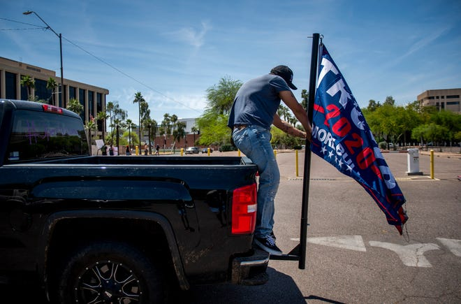 """Paul Armenta fixes a Trump flag on the back of his truck after protesting against shutting down the state during the novel coronavirus pandemic at the """"Operation Gridlock"""" at the Arizona state Capitol in Phoenix on April 19, 2020."""