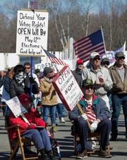 Protesters hold up signs on Sunday, April 19, 2020, at IROW Recycling in Mosinee, Wis. Hundreds gathered to call for Gov. Tony Evers to allow central Wisconsin businesses that are currently closed due to the COVID-19 pandemic to reopen.
