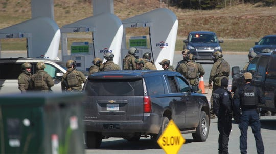 Royal Canadian Mounted Police prepare to take a person into custody at a gas station in Enfield, Nova Scotia, on April 19 after several people were harmed.