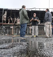 A man from the Bureau of Alcohol, Tobacco, Firearms & Explosives national response team talks with insurance representatives at the Marketplace Shopping Center Monday, a day after several businesses were damaged from the fire.