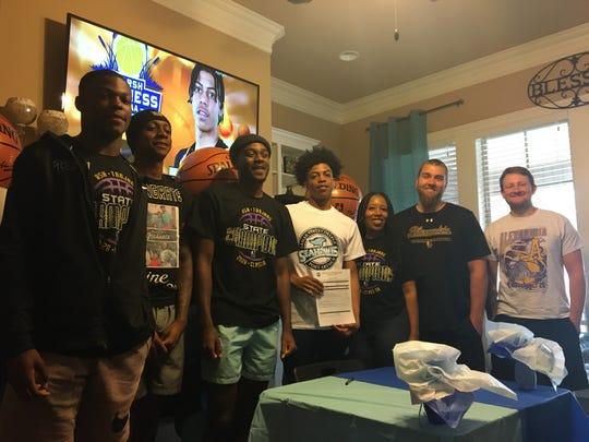 ASH senior guard Dez McQuain (center) signed with Lamar State of Port Arthur Sunday.