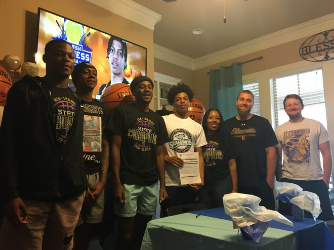 ASH senior guard Dez McQuain (center) signed with Lamar State of Port Arthur Sunday.