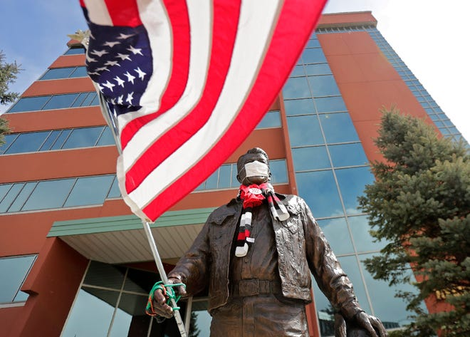 A statue of former President Ronald Reagan wears a mask and holds a flag in Neenah.