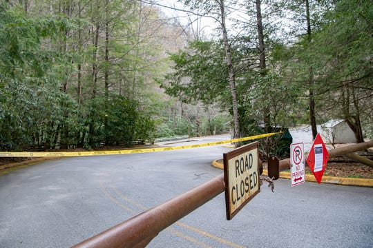 Caution tape is strung behind a barricade to block off the parking lot at Sliding Rock in the Pisgah National Forest on April 7, 2020. Most of the forest is now closed to help slow the spread of COVID-19.
