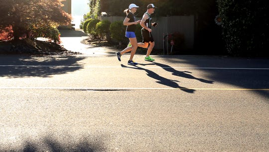 Tabatha Collins and John Spannuth run along Chico Way in Silverdale on Monday, April 20, 2020. The two runners, who both qualified for the Boston Marathon, logged the mileage in honor of the cancelled event.