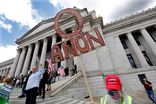 """A demonstrator holds a """"Q Anon"""" sign as he walks at a protest opposing Washington state's stay-home order to slow the coronavirus outbreak Sunday, April 19, 2020, in Olympia, Wash. Washington Gov. Jay Inslee has blasted President Donald Trump's calls to """"liberate"""" parts of the country from stay-at-home and other orders that are designed to combat the spread of the coronavirus. Inslee says that Trump is fomenting a potentially deadly """"insubordination"""" among his followers before the pandemic is contained. (AP Photo/Elaine Thompson)"""