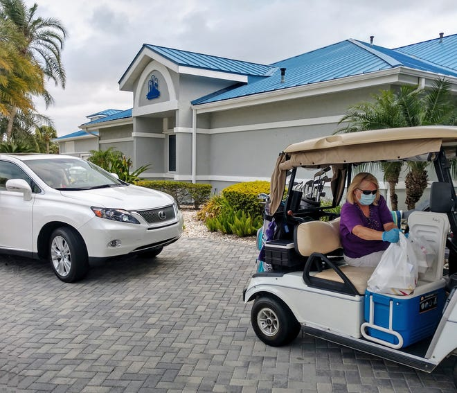 Indian River Colony Club member Pat Fuller picks up two of the special takeout Easter dinners prepared by the neighborhood's At Ease Club staff in Viera.